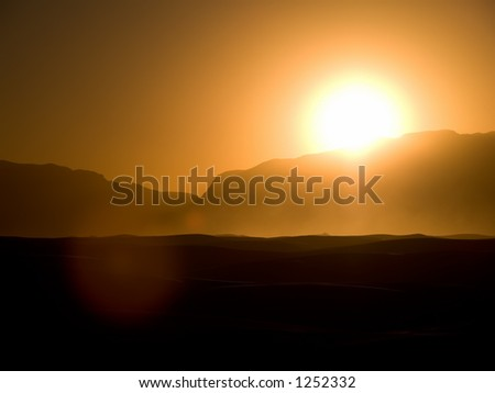 A high contrast view of the sunset over White Sands, New Mexico highlights the trails of glowing dust and sand rising over the crests of the dunes stirred by heavy winds preceeding dusk. - stock photo