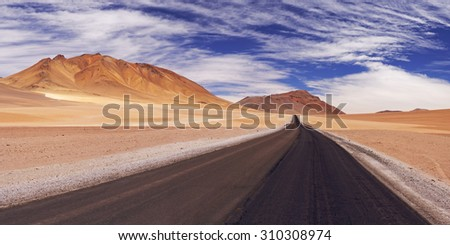 A high desert road through the Chilean Altiplano at an altitude of 4700m. - stock photo