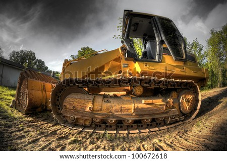 A High Dynamic Range fisheye photo of a bulldozer at a construction site. - stock photo