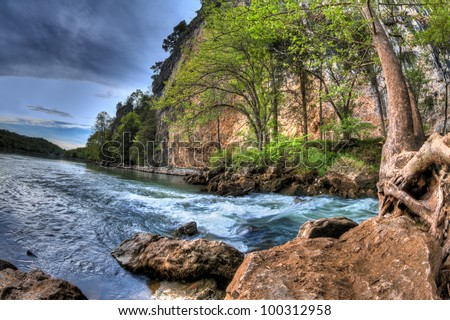A High Dynamic Range photo of a natural spring flowing into a lake - stock photo