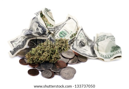 A high grade hydroponic Cannabis (Marijuana) bud resting on a pile of various USA coins - pennies, quarters, dimes, nickels, and 100 US$ dollar bills, on a white background.