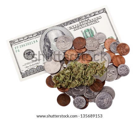 A high grade hydroponic Cannabis (Marijuana) bud resting on a pile of various USA coins - pennies, quarters, dimes, nickels, as well as a 100 US$ money note. White background, directly above.