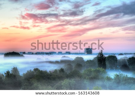 A high office building above the morning fog. The sun is rising creating vivid colors on the sky. - stock photo