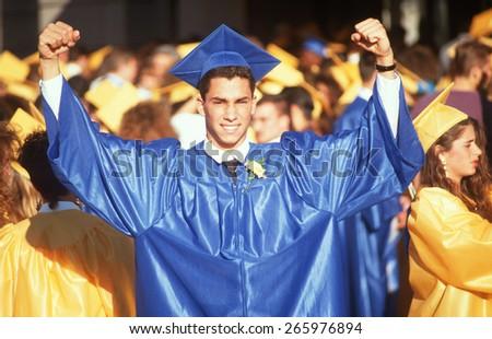 A high school graduate in victory pose, Providence, RI - stock photo