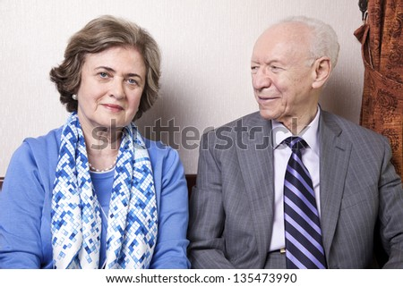 A high society senior couple (he's in his 80's, she's in her late 60's) sitting on a sofa. He's smiling and looking at her, and she's looking straight to the camera, with a slight smile on her face. - stock photo