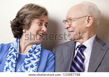 A high society senior couple (he's in his 80's, she's in her late 60's) sitting on a sofa looking at each other with very much love and joy. - stock photo