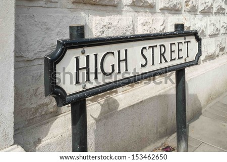 A High Street road sign in front of a white wall - stock photo