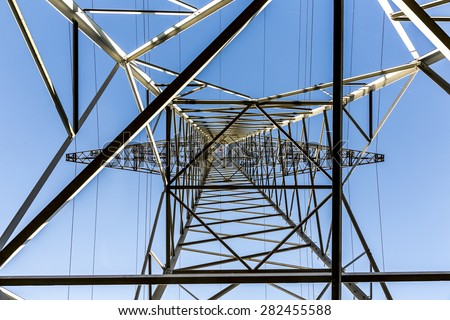 A high voltage electricity pylons against blue sky and cloud - stock photo