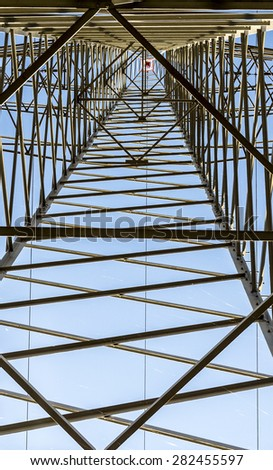 A high voltage electricity pylons against blue sky and cloud