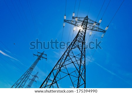 a high-voltage pylons for electricity against blue sky and sun rays - stock photo