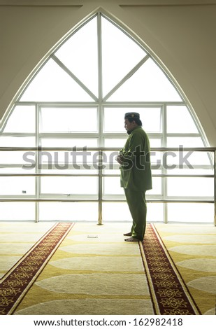 A highkey image of a Muslim prays  - stock photo
