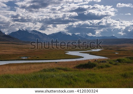 A highland river valley with yellow grass on a background of snow covered mountains and glaciers under white clouds and blue sky, Plateau Ukok, Altai mountains, Siberia, Russia