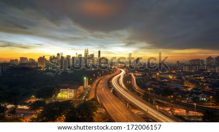 a highway lead to kuala lumpur city during sunset