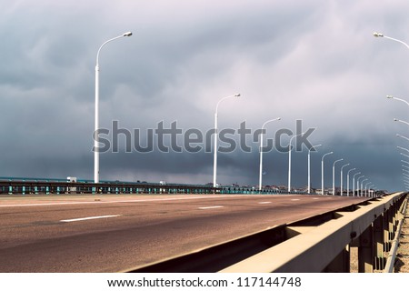 a highway under stormy clouds on the sky - stock photo
