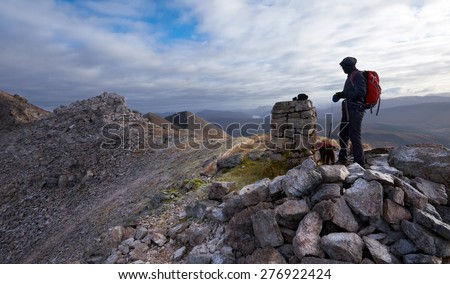 A hiker and their dog looking out over the summit of Beinn Eighe in the Scottish Highlands. - stock photo