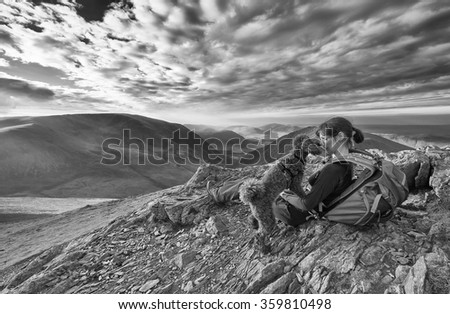 A hiker and their dog resting on a mountain summit. This image has added grain and styling. - stock photo
