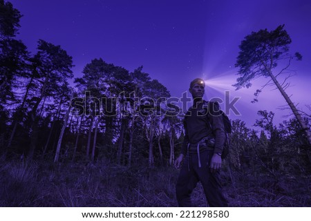 A hiker at night, wearing a head torch in a forest,under a starry sky. - stock photo