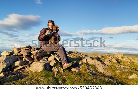 A hiker enjoying a hot drink with their dog on the summit of Place Fell in the English Lake District. UK.
