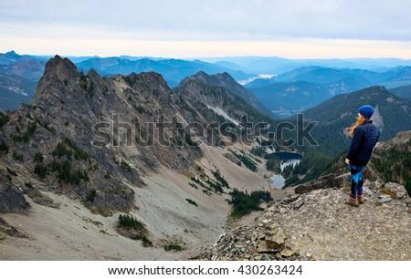 A Hiker Looking Towards Mountains and Alpine Lake.  Kaleetan Peak Trail, Snoqualmie Pass, Washington - stock photo