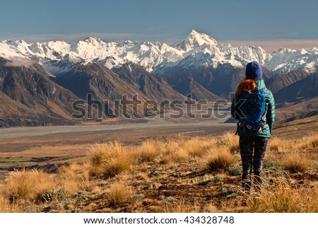 A Hiker Looks Towards The High and Snowy Southern Alps.  Hakatere Conservation Park, New Zealand - stock photo