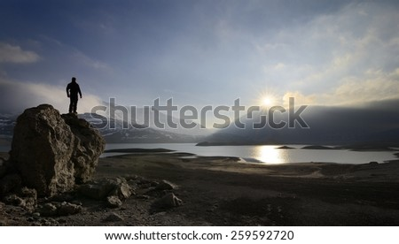 A hiker observes the Mont-Cenis lake( France ) in backlight - stock photo