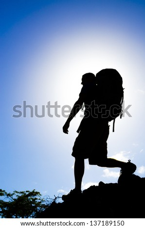 A hiker silhouetted against the sun. - stock photo