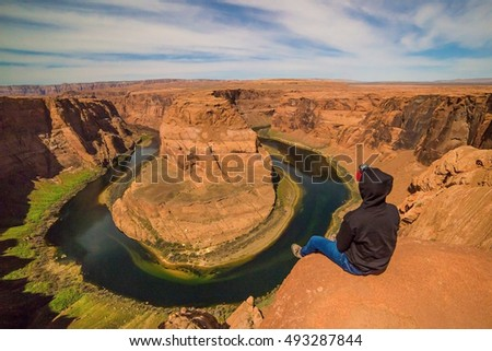 A hiker sitting at the edge of a cliff at Horseshoe Bend in Arizona