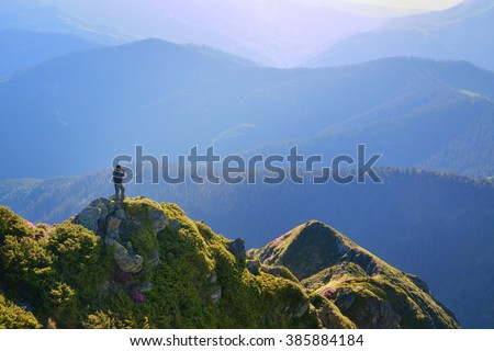 A hiker standing at cliff and taking photo of a view in summer mountains. - stock photo