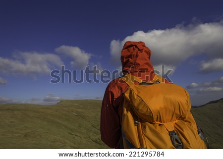 A hiker walks on top of mountains with a red jacket and orange backpack. Rear view, Lake District. UK. - stock photo