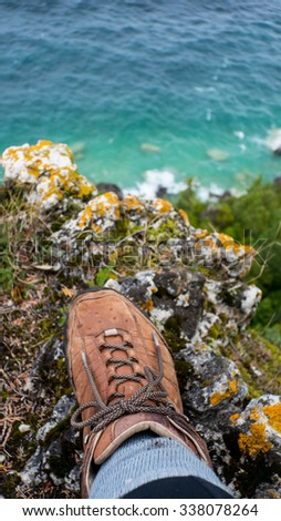A hikers boot is in the foreground near the precipice of a cliff with crystal blue water below - stock photo