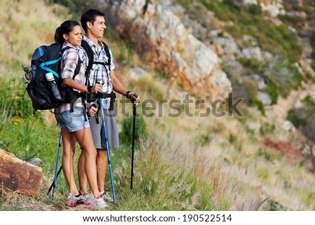 A hiking couple standing on a mountain range taking in the view with copyspace - stock photo