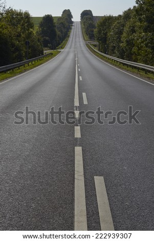 A hilly landscape with a straight road and bushes taken by contre-jour.