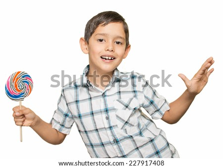 A Hispanic boy holds a lollipop and poses like he is dancing, or about to fly away. Isolated on a white background.  - stock photo
