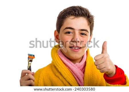 A Hispanic boy wears a yellow bathrobe with a pink towel around his neck: he has some patches on his face and smiling makes success sign while holding the razor used for shaving - stock photo