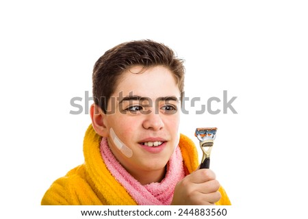 A Hispanic boy wears a yellow bathrobe with a pink towel around his neck: he has some patches on his face and smiling stares with crossed eyes at the razor he used for shaving - stock photo