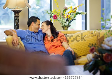 A hispanic man and a caucasian woman in jeans sit on a yellow couch cuddling and smiling at each other in their living room. - stock photo