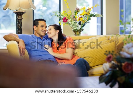 A hispanic man and a caucasian woman in jeans sit on a yellow couch cuddling in their living room with her looking up at him. - stock photo