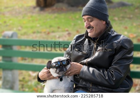 A Hispanic man sitting on a bench with a pug dog, enjoying playing with the dog and putting sunglasses on it.  - stock photo