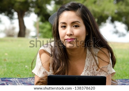 A Hispanic woman in the park with her tablet.