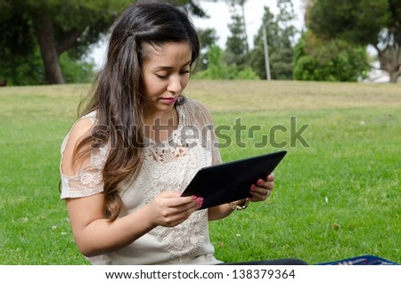 A Hispanic woman sitting in the park with her tablet. - stock photo