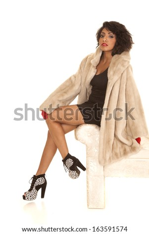 A Hispanic woman sitting on the edge of a bench, in her fur coat. - stock photo