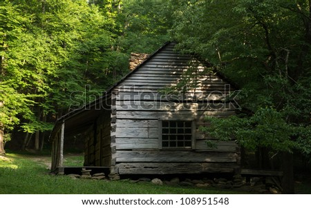 A historic cabin is surrounded by woods in the Smoky Mountain National Park. - stock photo