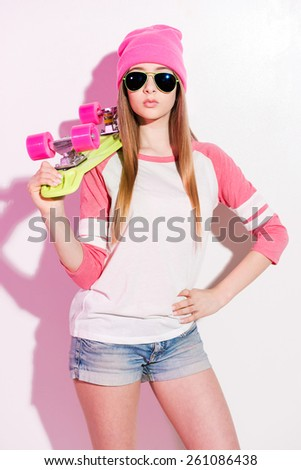 A hobby and a passion.  Playful young woman in pink headwear and sunglasses holding skateboard on her shoulder while standing against white background - stock photo