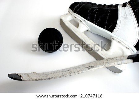 A hockey skate, puck and stick.