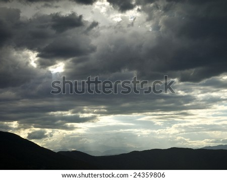 A hole in a stormy cloud let a ray of light pass trough. - stock photo
