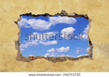 A Hole in a Wall with Blue Sky - stock photo