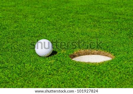 A hole over golf ball on green. Shallow depth of field. Focus on the ball and the hole. - stock photo