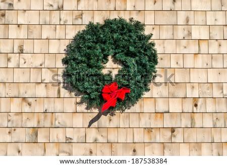 A holiday Christmas wreath on a wood cedar shingle wall. - stock photo