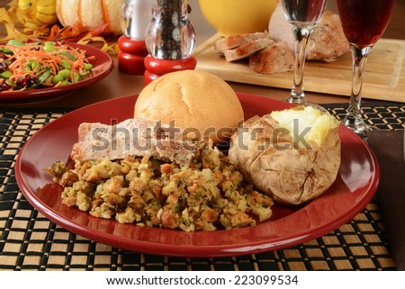 A holiday dinner with sliced turkey on stuffing with a healthy salad