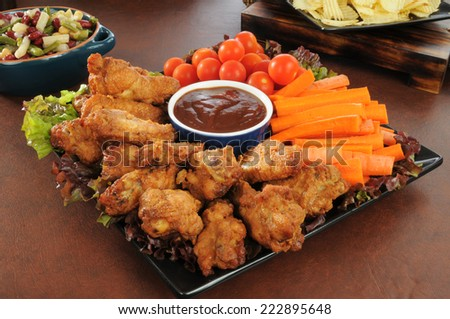 A holiday snack platter with chicken wings, carrot sticks, cherry tomatoes, salads, and chips - stock photo